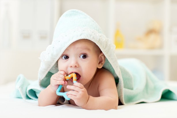 Baby with teething toy in mouth and towel on head