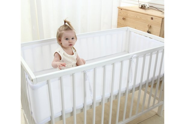 Baby in crib with bumpers