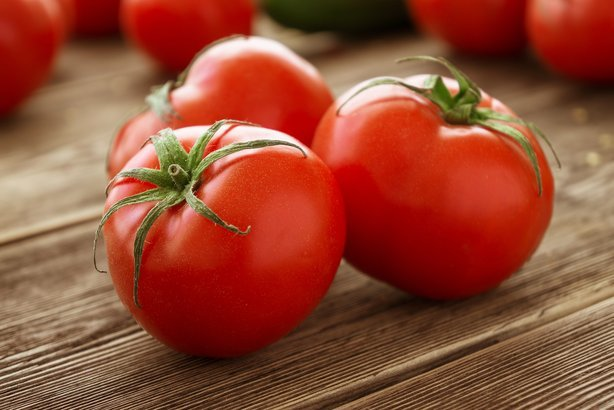 ripe tomatoes on wood background
