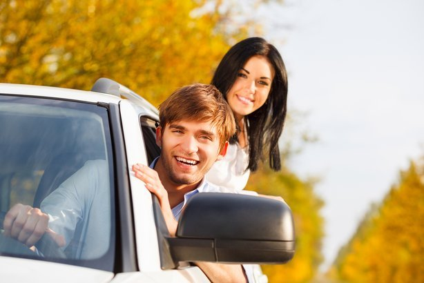young smile couple driving car in fall season