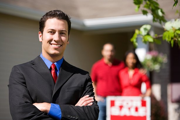 Happy real estate agent in front of home with buyers in background