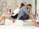 Exhausted couple sitting in house under construction back to back