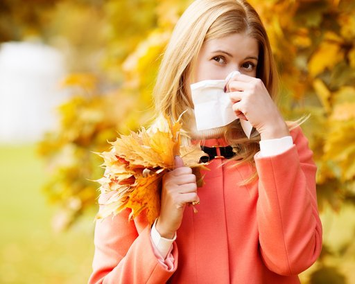 woman with cold rhinitis on autumn background