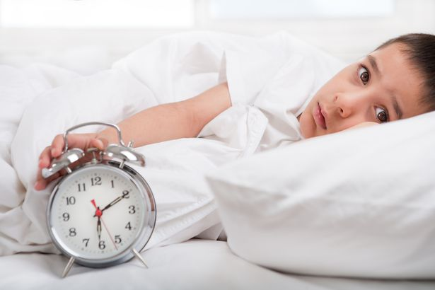 sleepless little boy laying in bed with clock