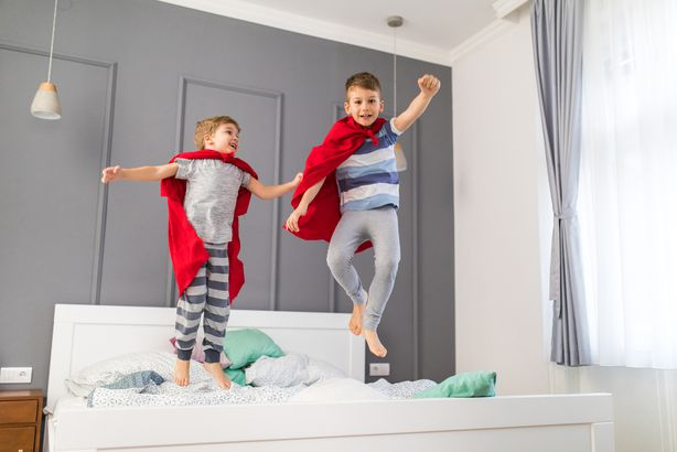two boys jumping on their bed