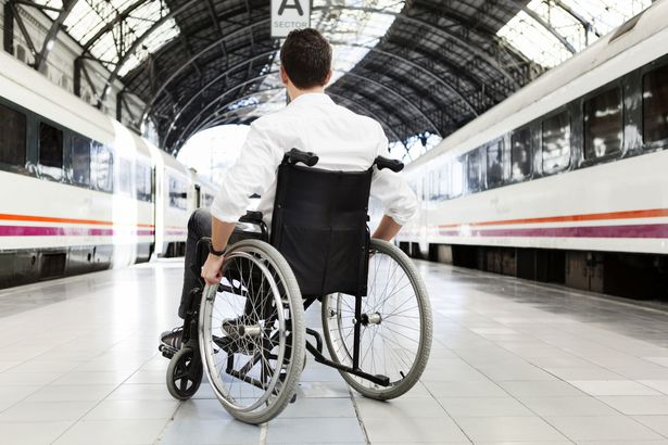 man win wheelchair on train platform with train on either side