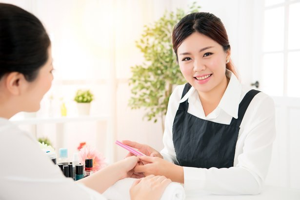 Happy smiling manicurist with a client