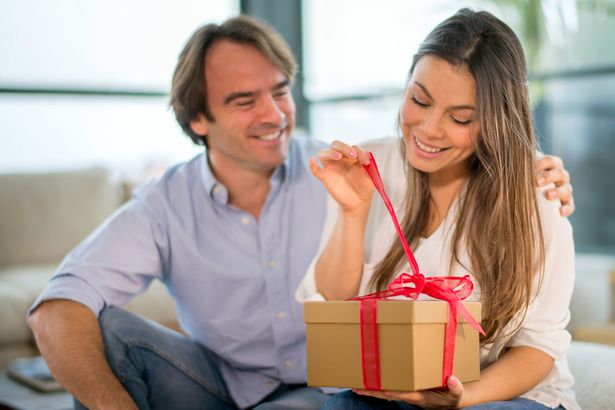 wife opening gift with her husband