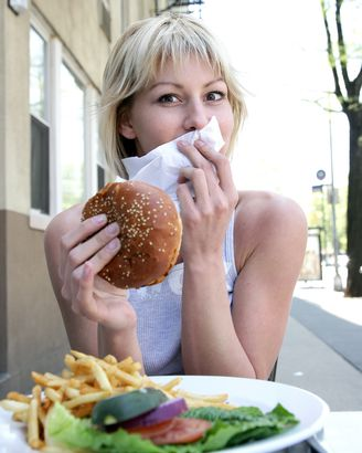 surprised woman eating a burger
