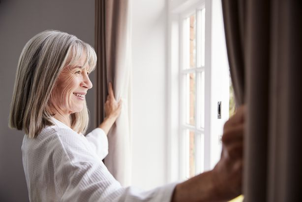 senior woman opening bedroom curtains and looking out of window