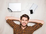 Top view of cheerful handsome man lying on floor with different devices