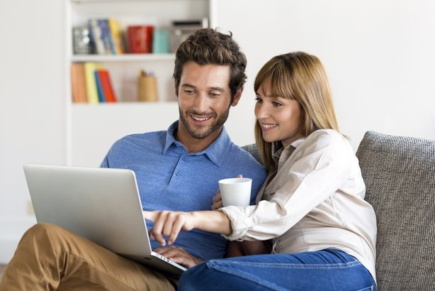 Couple surfing the web on a laptop at home
