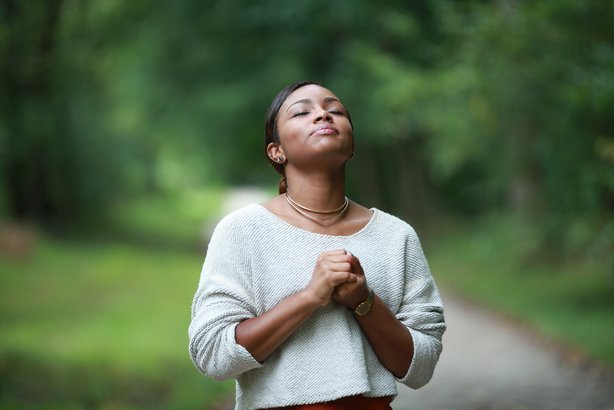 African American woman praying outside