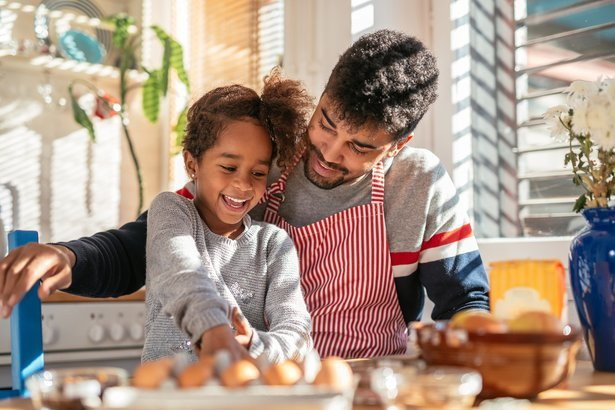 smiling African American father and daughter baking in the kitchen and having fun