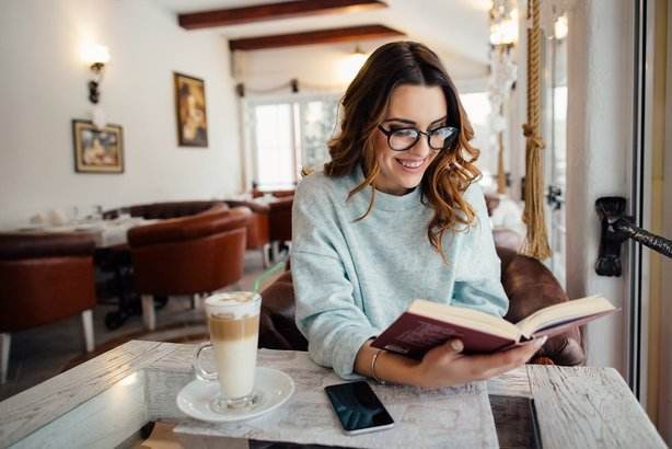 woman in glasses reading interesting book in cafe
