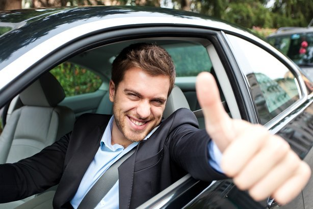 happy man giving thumbs up in his new car