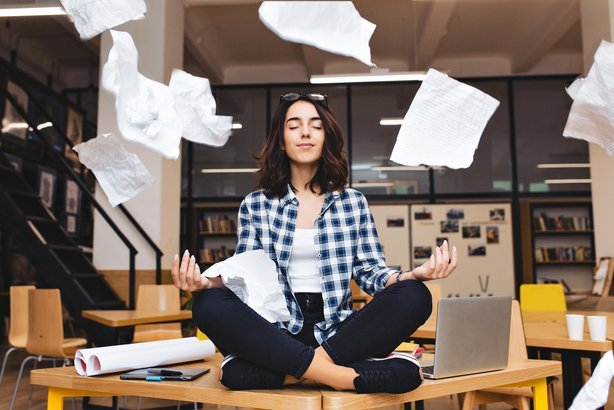 woman meditating on table surround work stuff and flying papers
