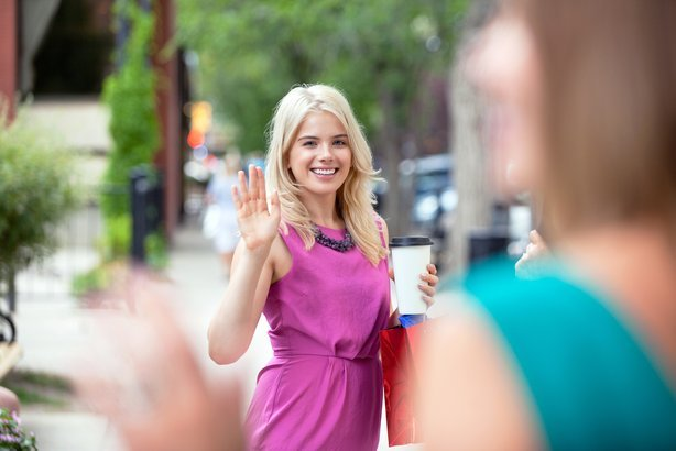 happy young woman with disposable coffee cup waving to friend