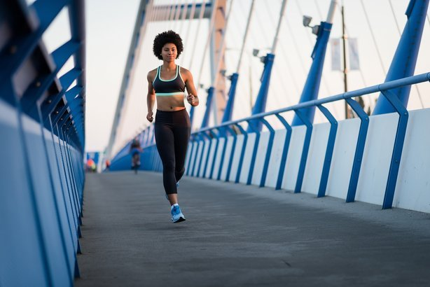 athletic woman runner in action during sunset