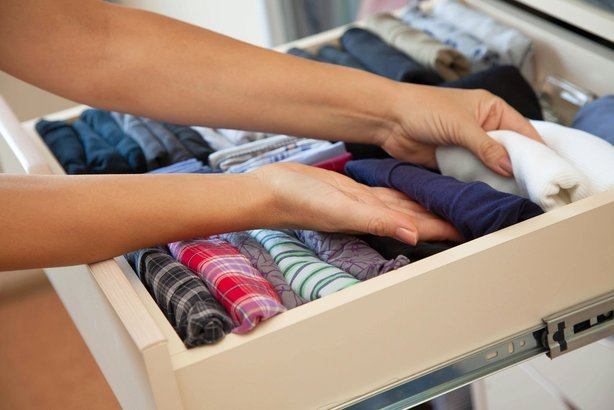 men going through neatly folded clothes in drawer