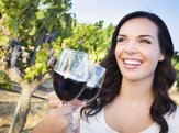 woman in a vineyard drinking wine