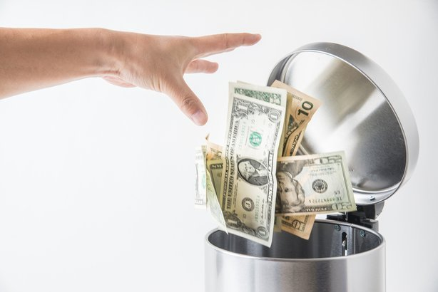 hand throwing away money in a trashcan