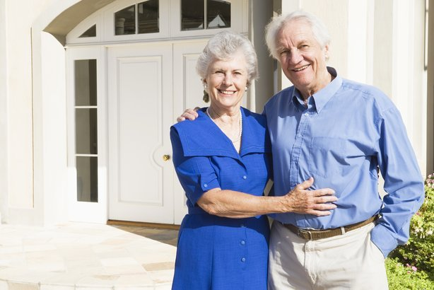 senior couple standing outside house