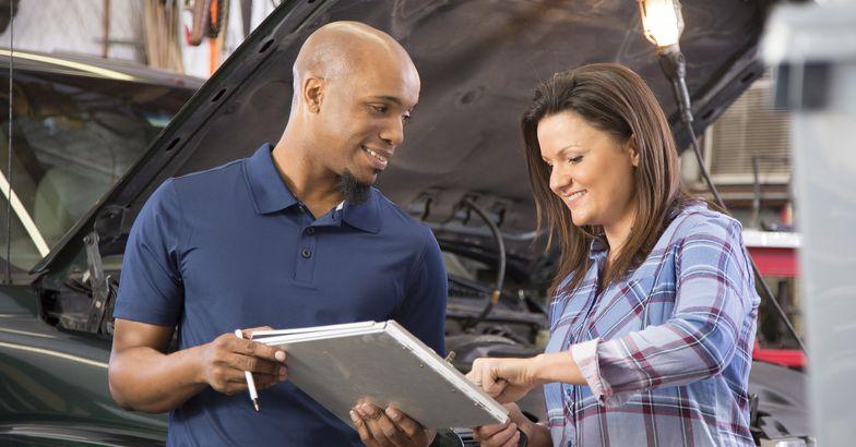 mechanic explains vehicle repair invoice to customer