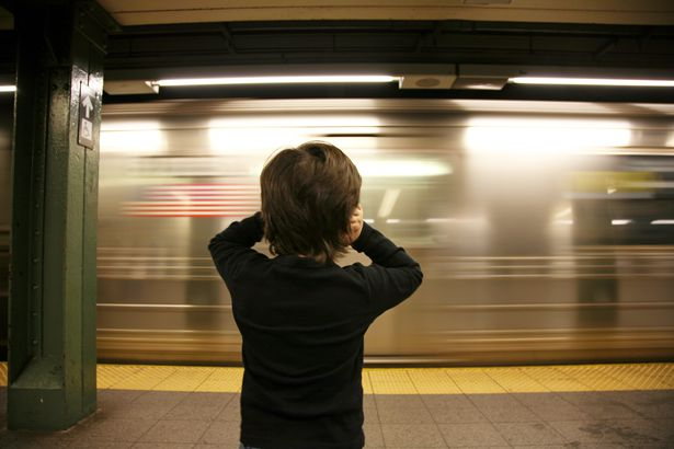 little child holding ears in face of nyc noisy nyc subway passing through station
