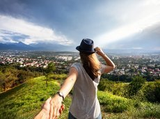 woman holding man by hand and looking to the city view in the mountains