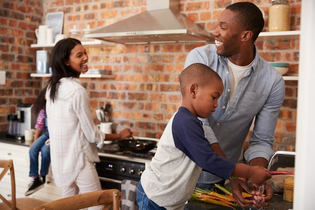 African American children helping parents to prepare meal in kitchen