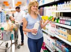 Beautiful woman customer choosing shampoo in cosmetics department