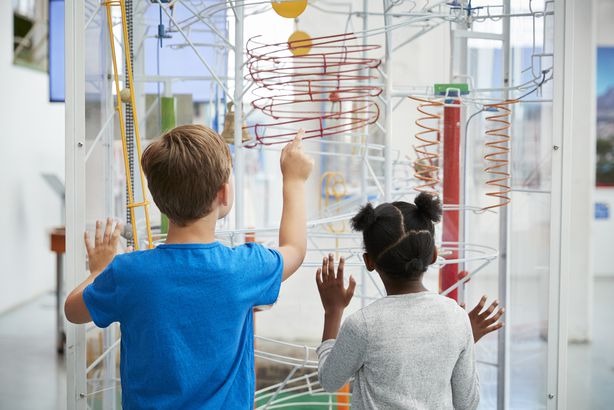 two kids looking at a science exhibit