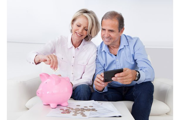 Happy older couple putting coins in a piggy bank
