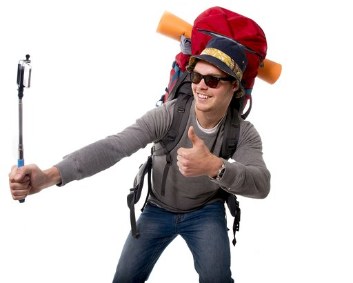 young attractive backpacker tourist taking selfie photo with stick carrying backpack