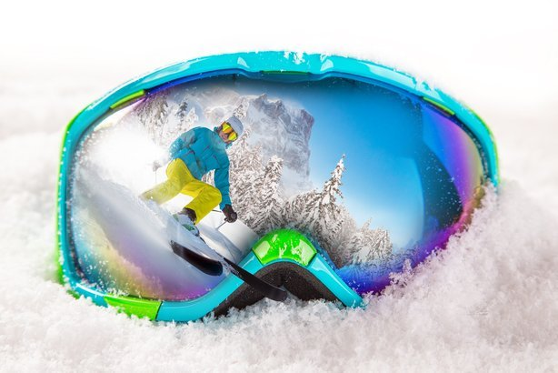 colorful ski glasses with skier on snow