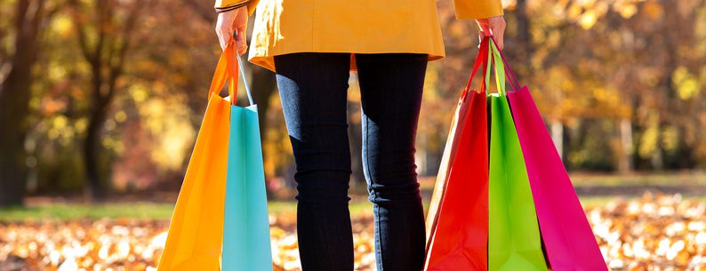 woman holding colorful shopping bags in autumn
