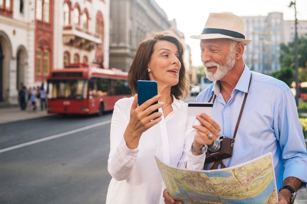 older couple smiling looking at card and map in travel destination