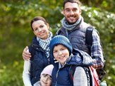 happy family walking with backpacks in woods