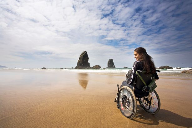 young woman in wheelchair on beach in pacific coast of united states