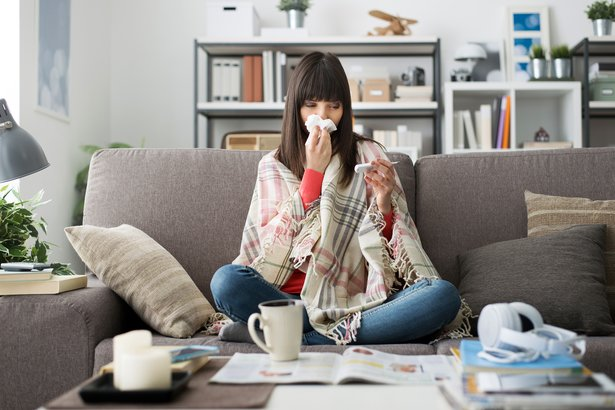 Sick woman with cold or flu sitting on the sofa at home taking her temperature