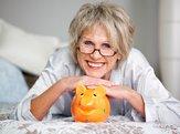 Happy senior female lying on bed with piggybank