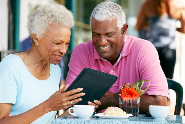 African American couple looking at tablet in a cafe