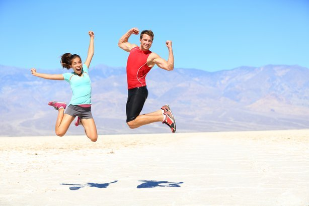 couple jumping happy and energetic in desert landscape