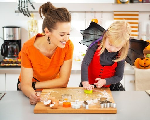 Halloween dressed girl with young mother in decorated kitchen