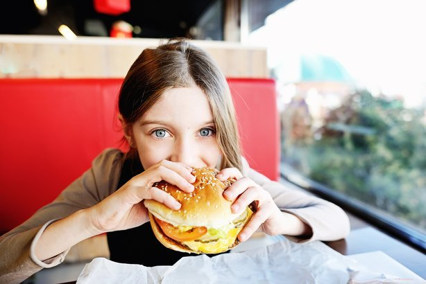 girl in school uniform eating a hamburger in the restaurant