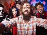man taking selfie of group of people during Halloween costume party