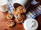 Assorted cookies falling out of a jar on a wooden table with a glass of milk