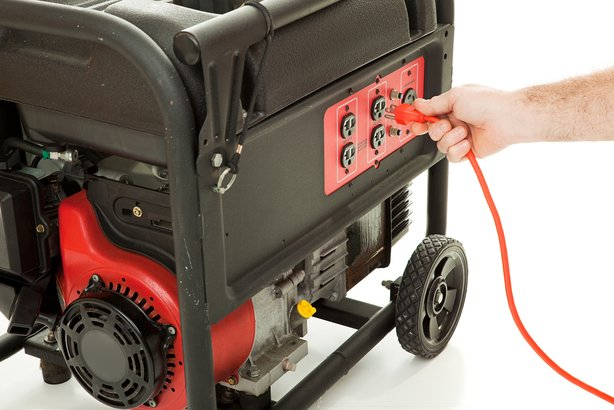 man's hand plugging an extension cord into an emergency generator
