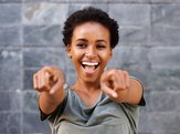 Attractive young black woman smiling and pointing at camera